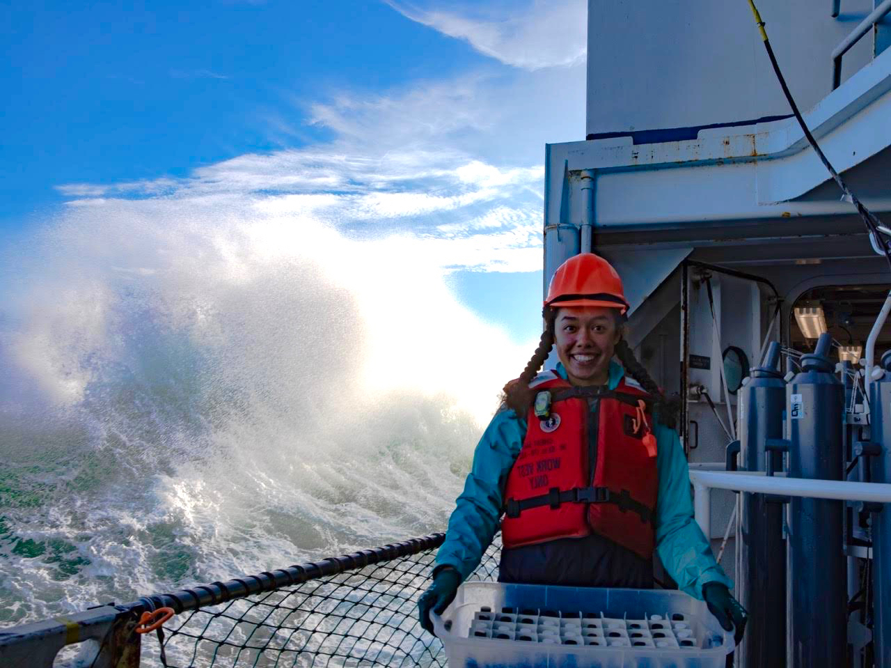 Carina holding a rack of water samples on a research vessel with a giant wave swell behind her.
